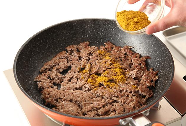 3.別のフライパンにサラダ油(大さじ1)を熱し、豚挽き肉を加えて炒める。 豚肉の色が変わったらカレー粉を加え、豚肉の脂とカレー粉がなじんで黄色い脂が出てくるまでしっかりと炒めて(2)に加える。