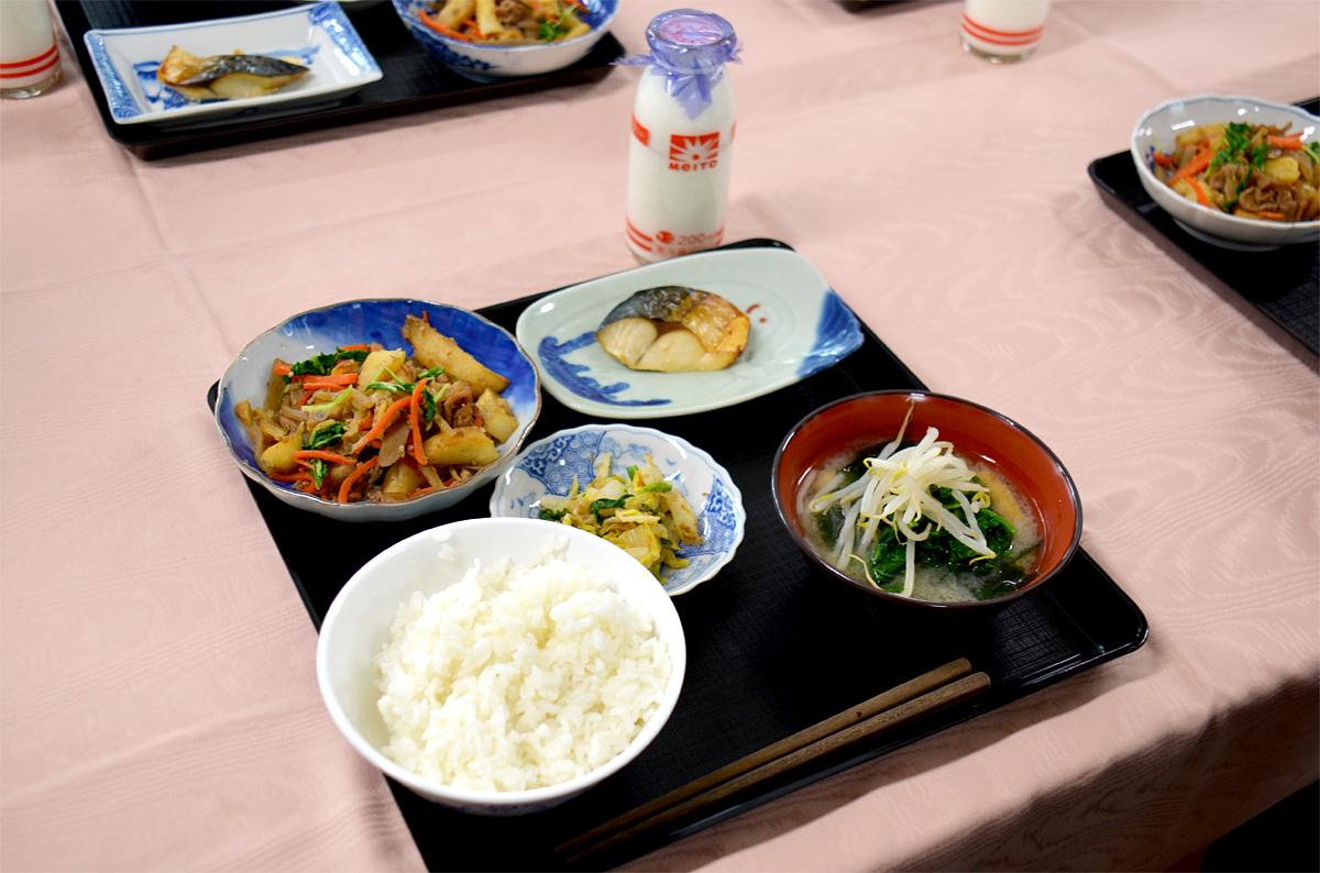 """メニューは、通常の和食給食にプラスして、温かいみそ汁とデザートが付き、「ご飯、みそ汁、サバの文化干し、じゃがいものきんぴら煮、おひたし、白玉だんご、果物(いちご・オレンジ)」といった、一汁三菜プラスαの""""和食膳""""。"""