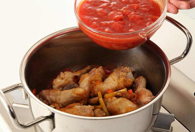 (1)のパプリカ・(2)の鶏手羽元・トマト水煮を加え、しっかりと炒める。ブイヨン・ローリエ・マッシュルームを加え、弱火で20分煮る